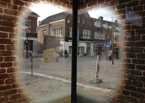 Glass walls printed with red brick texture imitations and controlled opacity of ink to create window frame effects